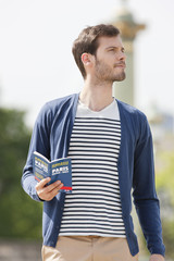 Man holding a travel guidebook, Paris, Ile-de-France, France