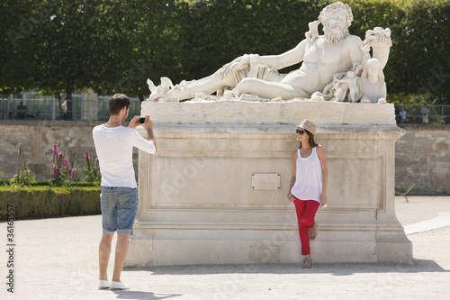 Man taking a picture of a woman standing near a sculpture in a garden, Jardin des Tuileries, Paris, Ile-de-France, France