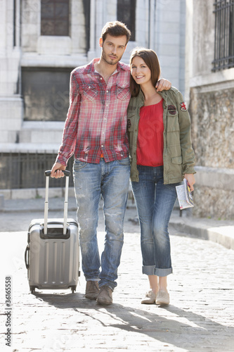 Couple walking on a road with a suitcase, Paris, Ile-de-France, France