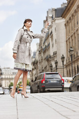 Woman hailing a taxi, Paris, Ile-de-France, France