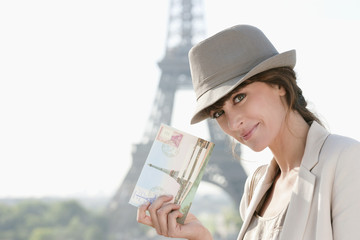 Woman showing a postcard with the Eiffel Tower in the background, Paris, Ile-de-France, France