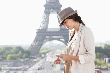 Woman reading a guide book with the Eiffel Tower in the background, Paris, Ile-de-France, France
