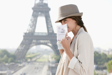 Woman holding a guide book with the Eiffel Tower in the background, Paris, Ile-de-France, France