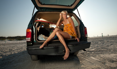 Young Blonde Woman sitting in the back of her truck on the beach