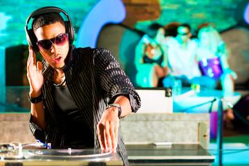 DJ im Club mit Menge im Hintergrund