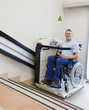 man in an invalid chair walks upstairs