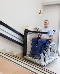 man in an invalid chair walks upstairs
