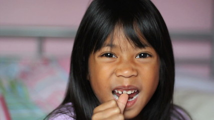 Asian Girl Wiggling Her First Loose Tooth