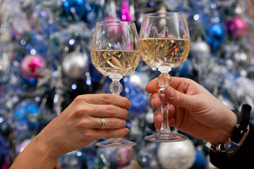 Hands holding glasses of champagne against new year tree