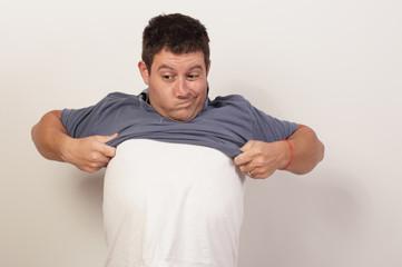 Man struggling to remove his shirt