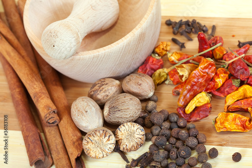 various natural spices with pestle and mortar