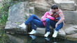 Young couple kissing on rocks by water