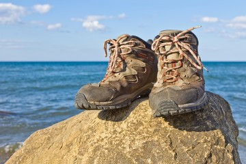 pair of touristic boots on a sea coast