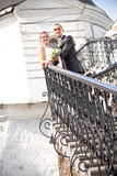 couple posing standing on long stairs with handrail poster
