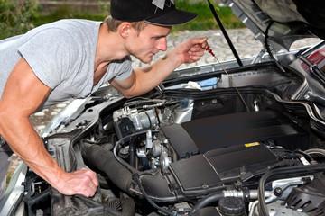 Junger Mann blickt unter die Motorhaube vom PKW