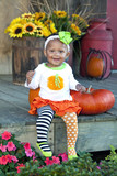 One year old girl with pumpkins and flowers
