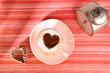 cappuccino with old alarm clock and heart on red stripy backdrop
