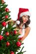 Frau in Dessous schaut hinter Weihnachtsbaum hervor