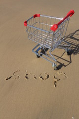 Retail cart, near the sea water - with the word SHOP