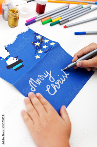 Child writing christmas greeting card