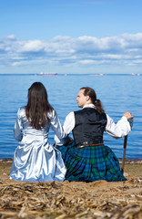 Woman and man in in scottish costume near the sea
