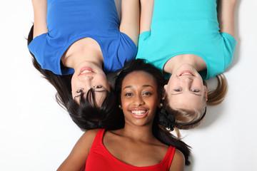 Three mixed race teenage girl friends on floor