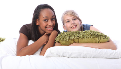 Black and white teenage girl friends lying on bed