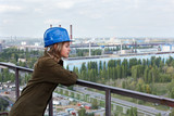 Worker female in factory standing in helmet on altitude poster