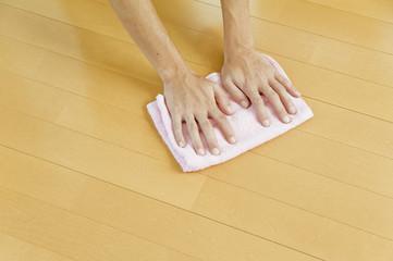 床を拭き掃除する人物の手のアップ
