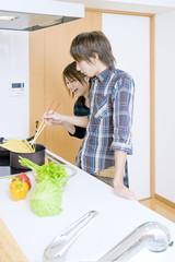 キッチンで料理をする若い男女のカップル