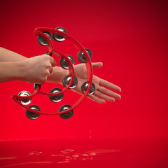 hands holding tambourine on red background