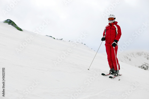 Woman skier standing on mountain slope