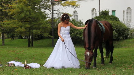Beautiful bride and horse walking in the park