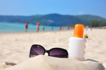 Sunglasses and protection lotion on the beach