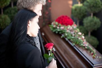 Paar bei Beerdigung mit Sarg