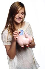 młoda dziewczyna wrzucająca pieniądze do skarbonki