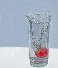 Strawberry Splashing into Glass of Sparkling Water