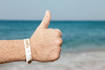 Hand gesturing thumb up on sea beach