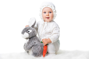 cute infant girl playing with toy rabbit isolated on white
