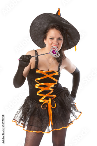 smiling girl in Halloween witch with wand