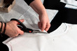 Woman hand cutting fabric after a sewing pattern
