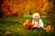 toddler girl have fun playing with fallen golden leaves