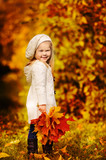 Fototapety little girl in warm cardigan smiling against the background of f