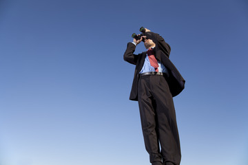 Businessman searching with his binoculars