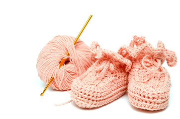 pink crocheted babby's bootees and thread with crochet