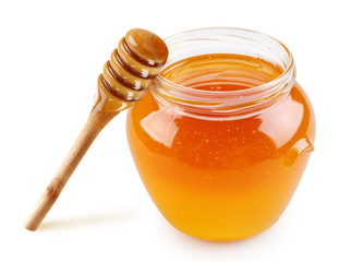 Honey in a glass jar with a stick