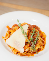 Pasta with tomato sauce, slice of parmesan, thyme and rosemary