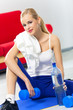 Woman with dumbbells, water and terry towel