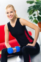 Woman exercising with dumbbell on fit ball
