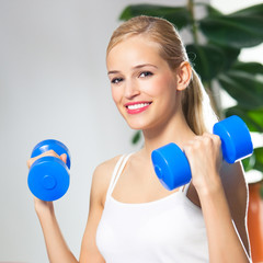 Woman exercising with dumbbells, at home